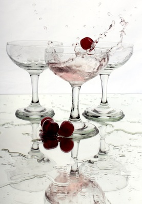 Champagne glasses with liquid and raspberries splashing