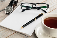 Blank paper with pen, glasses, watch and a cup of tea