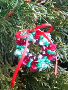 Beaded Wreath Ornament handing on an evergreen branch