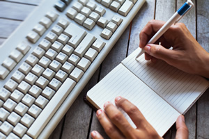 A hand writing in a journal near a computer keyboard.