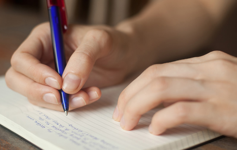 Woman's hand with a pen writing in a journal